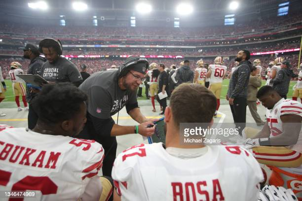 Defensive Line Coach Kris Kocurek of the San Francisco 49ers talks wit the defensive line on the sidelines during the game against the Arizona...