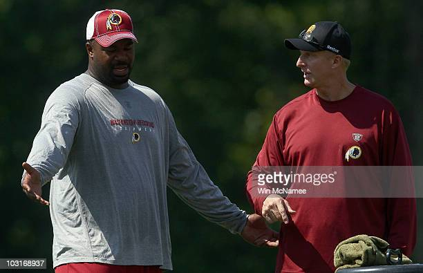 Defensive lineman Albert Haynesworth of the Washington Redskins works out with defensive coordinator Jim Haslett following practice on the second day...