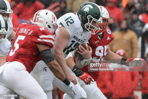 Defensive lineman Ben Stille of the Nebraska Cornhuskers and linebacker Dedrick Young II wrap up quarterback Rocky Lombardi of the Michigan State...