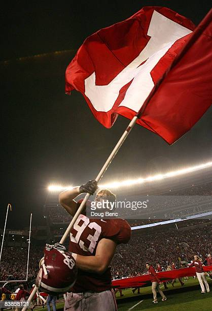 Defensive lineman Bobby Greenwood of the Alabama Crimson Tide waves an Alabama flag after defeating the Auburn Tigers at BryantDenny Stadium on...