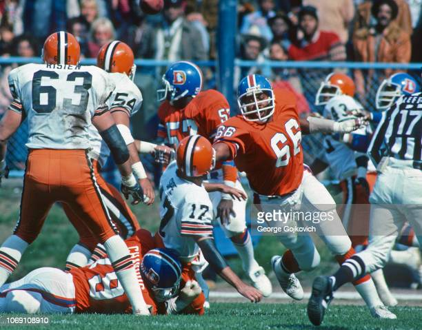 Defensive lineman Brison Manor of the Denver Broncos pursues the play as defensive lineman Barney Chavous tackles quarterback Brian Sipe of the...
