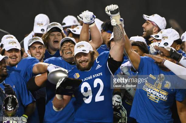 Defensive lineman Cade Hall of the San Jose State Spartans raises the Mountain West Championship game defensive MVP trophy after the team defeated...