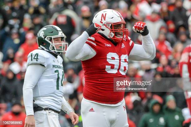 defensive lineman Carlos Davis of the Nebraska Cornhuskers cheers a missed field goal as holder Brian Lewerke of the Michigan State Spartans looks on...