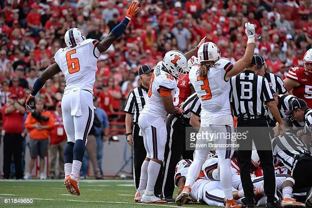 Defensive lineman Carroll Phillips of the Illinois Fighting Illini celebrates a turnover with defensive back Taylor Barton and linebacker Hardy...