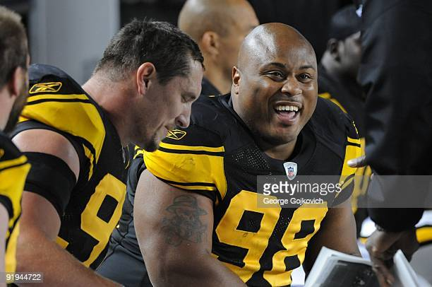 Defensive lineman Casey Hampton of the Pittsburgh Steelers smiles as he sits next to Aaron Smith on the sideline during a game against the San Diego...