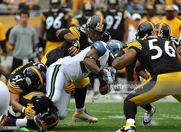 Defensive lineman Casey Hampton of the Pittsburgh Steelers tackles running back Marshawn Lynch of the Seattle Seahawks with assistance from...