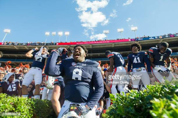 Defensive lineman Coynis Miller Jr #8 of the Auburn Tigers celebrates with teammates after defeating the Texas AM Aggies at JordanHare Stadium on...