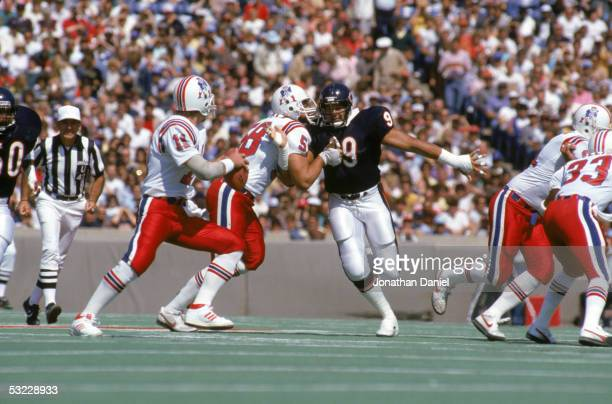 Defensive lineman Dan Hampton of the Chicago Bears attempts to reach quarterback Tony Eason of the New England Patriots as he battles with offensive...