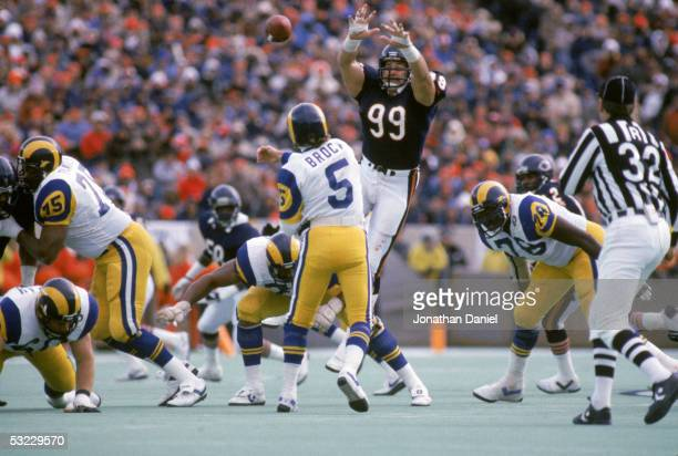 Defensive lineman Dan Hampton of the Chicago Bears jumps up in the air in an attempt to block a pass by quarterback Dieter Brock of the Los Angeles...