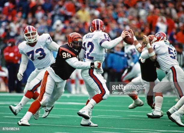 Defensive lineman David Grant of the Cincinnati Bengals sacks quarterback Jim Kelly of the Buffalo Bills as offensive lineman Will Wolford looks on...