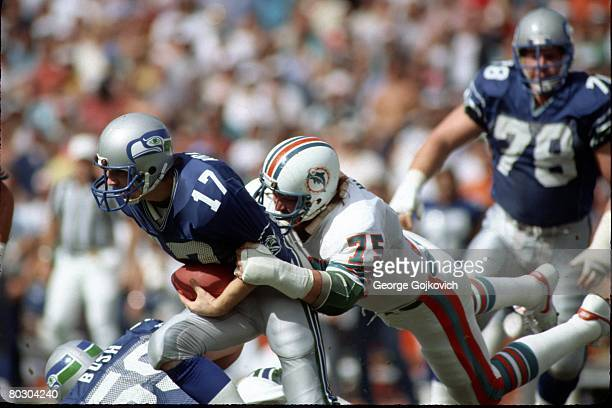 Defensive lineman Doug Betters of the Miami Dolphins sacks quarterback Dave Krieg of the Seattle Seahawks during a playoff game at the Orange Bowl on...