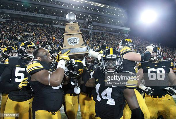 Defensive lineman Faith Ekakitie and defensive back Desmond King of the Iowa Hawkeyes celebrate with the Heroes Trophy after defeating the Nebraska...