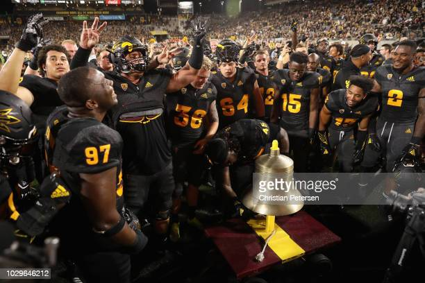 Defensive lineman George Lea of the Arizona State Sun Devils rings the bell in celebration with teammates after defeating the Michigan State Spartans...