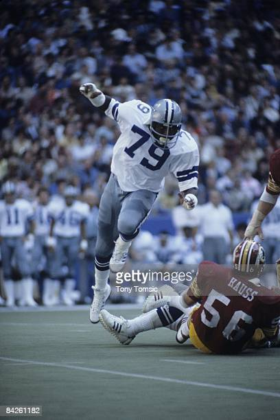 Defensive lineman Harvey Martin of the Dallas Cowboys leaps over the legs of the lineman on the ground during a game on December 13 1975 against the...