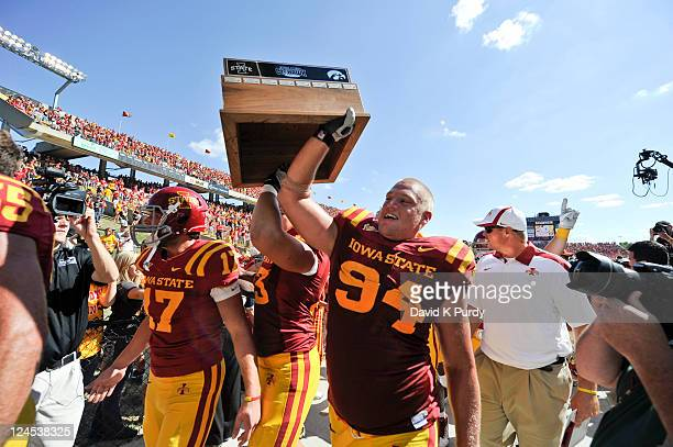 Defensive lineman Jake McDonough and his teammates carry the Iowa Corn CyHawks trophy off the field after defeating the University of Iowa Hawkeyes...