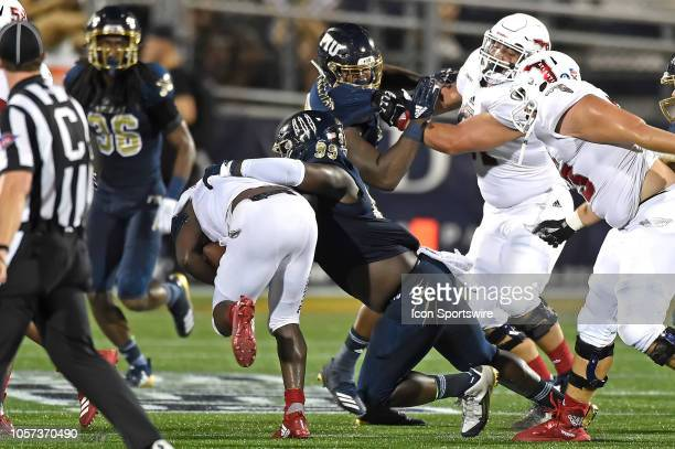 FIU defensive lineman Jermaine Sheriff tackles FAU running back Devin Singletary in the third quarter as the FIU Golden Panthers faced the Florida...