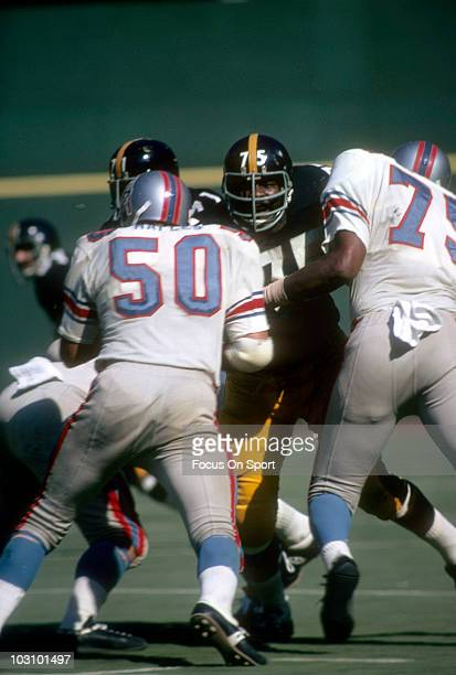 Defensive lineman Joe Greene of the Pittsburgh Steelers battles an offensive linemen Bobby Maples and Elbert Drungo of the Houston Oilers circa 1970...
