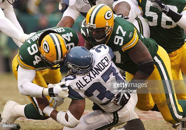 Defensive lineman Kabeer GbajaBiamila and Cletidus Hunt of the Green Bay Packers stop running back Shaun Alexander of the Seattle Seahawks on January...