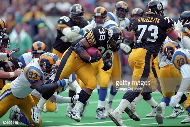 Defensive lineman Kevin Carter of the St Louis Rams tackles running back Jerome Bettis of the Pittsburgh Steelers as offensive lineman Justin...