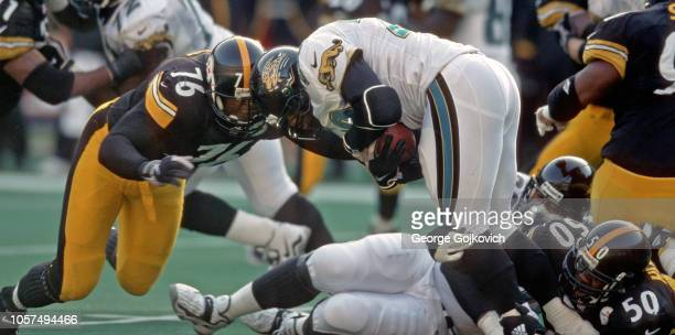 Defensive lineman Kevin Henry and linebacker Earl Holmes of the Pittsburgh Steelers tackle running back Fred Taylor of the Jacksonville Jaguars...