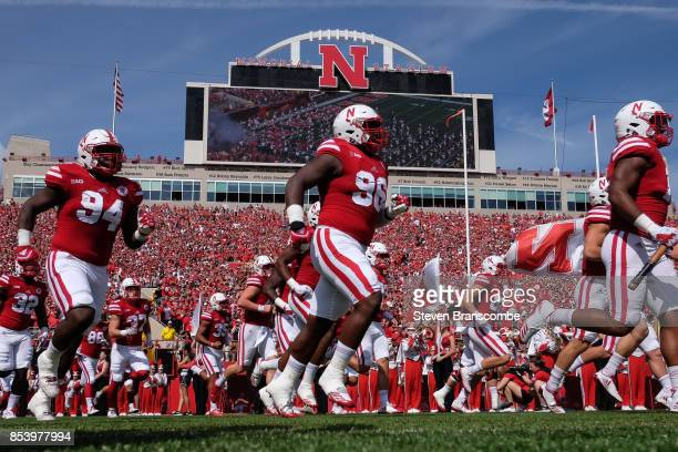 Defensive lineman Khalil Davis of the Nebraska Cornhuskers and defensive lineman Carlos Davis run on the field before the game against the Rutgers...