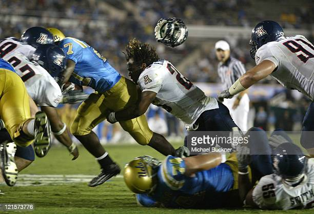 Defensive lineman Kirk Johnson of the University of Arizona loses his helmet while tackling tailback Chris Markey of UCLA during the of the 3717 win...