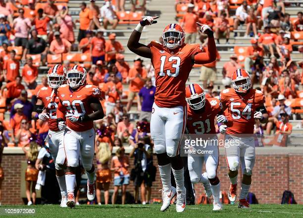 Defensive lineman KJ Henry of the Clemson Tigers reacts as he runs off the field with teammates safety Nolan Turner linebacker Jalen Williams...
