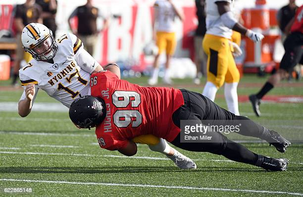 Defensive lineman Mike Hughes Jr #99 of the UNLV Rebels tackles quarterback Josh Allen of the Wyoming Cowboys after he threw the ball during their...