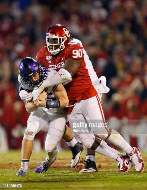 Defensive lineman Neville Gallimore of the Oklahoma Sooners brings down quarterback Max Duggan of the TCU Horned Frogs for a loss of a yard in the...