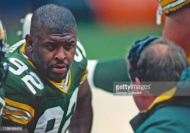 Defensive lineman Reggie White of the Green Bay Packers talks to head coach Mike Holmgren on the sideline during a game against the Cleveland Browns...