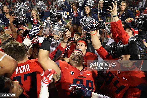 Defensive lineman Sani Fuimaono of the Arizona Wildcats celebrates with the Territorial Cup after defeating the Arizona State Sun Devils 5635 in...