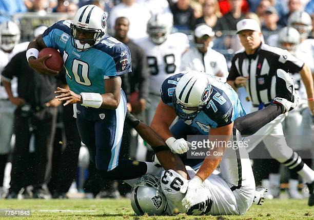 Defensive lineman Tommy Kelly of the Oakland Raiders battles against offensive tackle David Stewart as he tackles quarterback Vince Young of the...