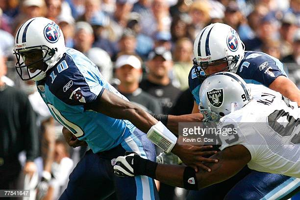 Defensive lineman Tommy Kelly of the Oakland Raiders battles against offensive tackle David Stewart as he tries to tackle quarterback Vince Young of...