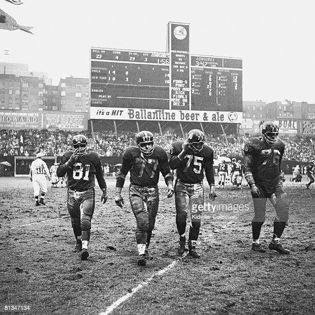 Defensive linemen Andy Robustelli Dick Modzelewski Jim Katcavage and Roosevelt Grier of the New York Giants walk towards the sidline during the third...