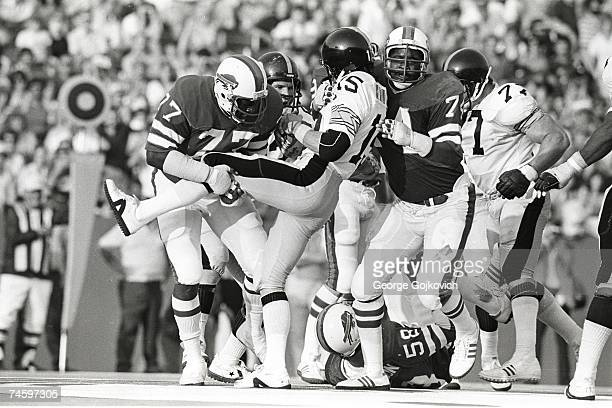 Defensive linemen Ben Williams and Dee Hardison of the Buffalo Bills tackle quarterback Mike Kruczek of the Pittsburgh Steelers during a preseason...
