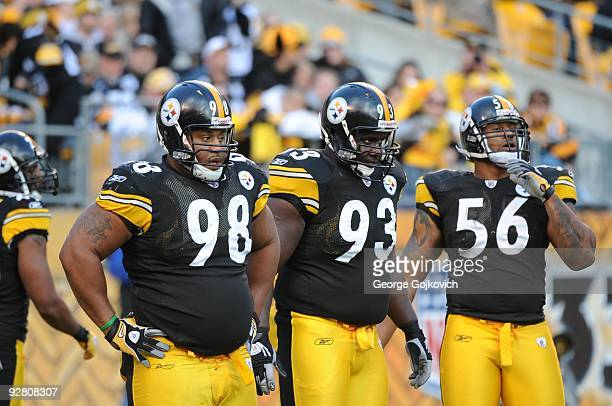 Defensive linemen Casey Hampton and Nick Eason and linebacker LaMarr Woodley of the Pittsburgh Steelers look on from the field during a game against...