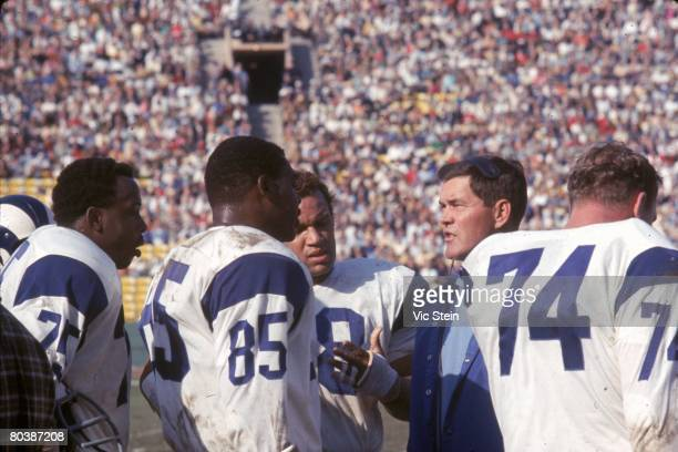 Defensive linemen Deacon Jones Lamar Lundy Roger Brown and Merline Olsen of the the Los Angeles Rams listen to defensive coach Marion Campbell during...