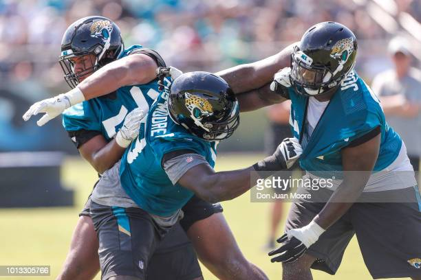 Defensive Linemen Eli Ankou Kapron LewisMoore and Abry Jones of the Jacksonville Jaguars works out during Training Camp at Dream Finders Homes...