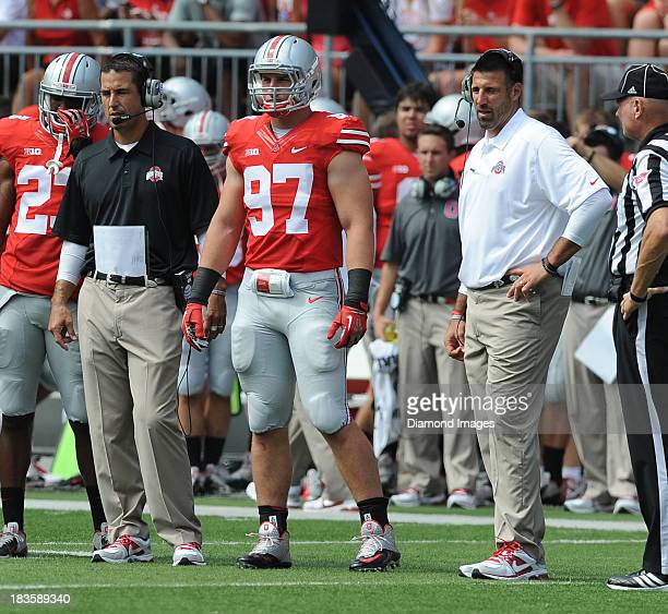 Defensive linemen Joey Bosa of the Ohio State Buckeyes stands on the field between coaches Luke Fickell and Mike Vrabel during a game against the...