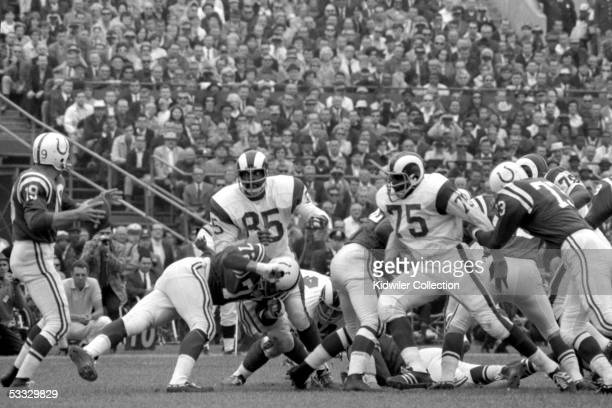 Defensive linemen Lamar Lundy and Deacon Jones of the Los Angeles Rams try to get to quarterback Johnny Unitas of the Baltimore Colts during a game...
