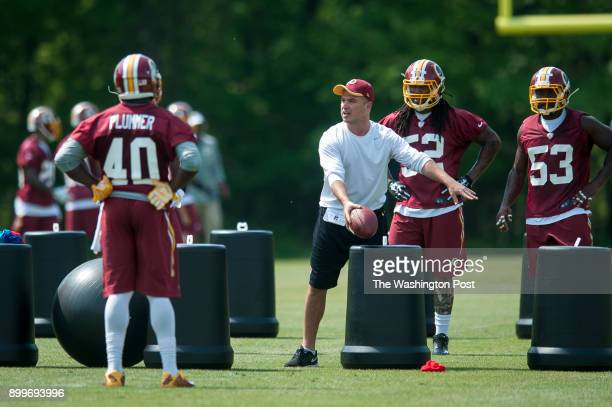 Defensive Quality Control Coach Chad Grimm works with players during a Washington Redskins rookie minicamp on Saturday May 16 2015 in Ashburn Virginia