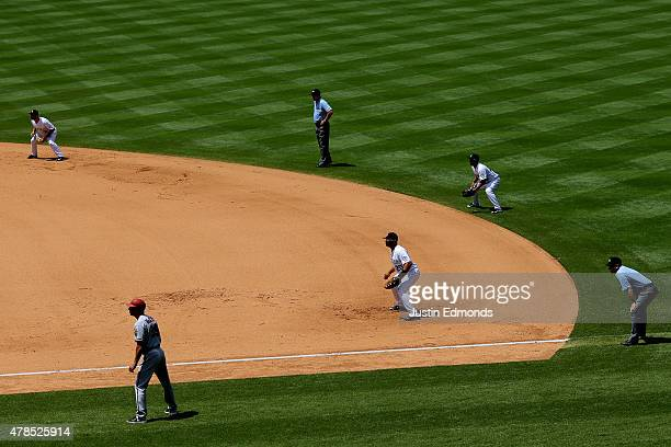 A defensive shift makes for a busy right side of the diamond including shortstop Daniel Descalso of the Colorado Rockies first base coach Dave McKay...