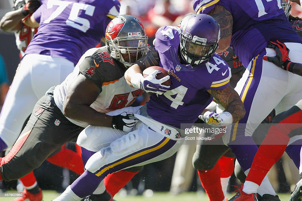 Defensive tackle Akeem Spence #97 of the Tampa Bay Buccaneers tackles running back Matt Asiata #44 of the Minnesota Vikings during the third quarter at Raymond James Stadium on October 26, 2014 in Tampa, Florida.