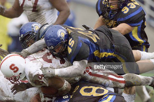 Defensive tackle Brandon Miles of the San Jose State Spartans lands on top of runningback Brian Allen in a pileup during the NCAA game against the...