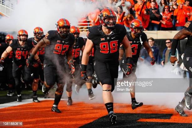 Defensive tackle Brendon Evers defensive tackle Cameron Murray and linebacker Kenneth EdisonMcGruder of the Oklahoma State Cowboys lead the team onto...