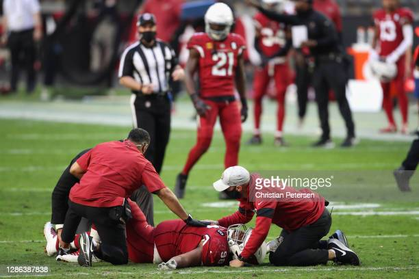 Defensive tackle Corey Peters of the Arizona Cardinals is looked at by team trainers after an injury against the Buffalo Bills during the NFL game at...