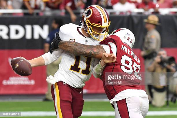Defensive tackle Corey Peters of the Arizona Cardinals tackles quarterback Alex Smith of the Washington Redskins during the third quarter at State...
