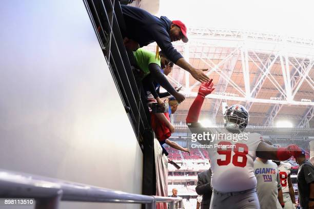 Defensive tackle Damon Harrison of the New York Giants high fives fans as he walks off the field before the NFL game against the Arizona Cardinals at...