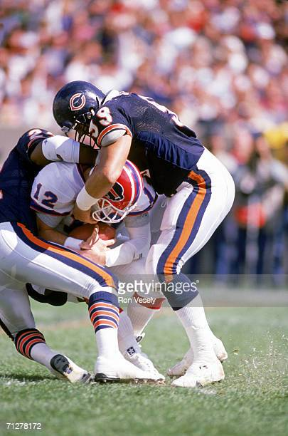 Defensive tackle Dan Hampton of the Chicago Bears combines with a teammate to sack quarterback Jim Kelly of the Buffalo Bills at Soldier Field on...