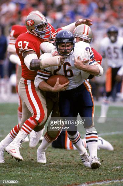 Defensive tackle Gary Johnson and linebacker Riki Ellison of the San Francisco 49ers stop Chicago Bears running back Matt Suhey during the 1984 NFC...